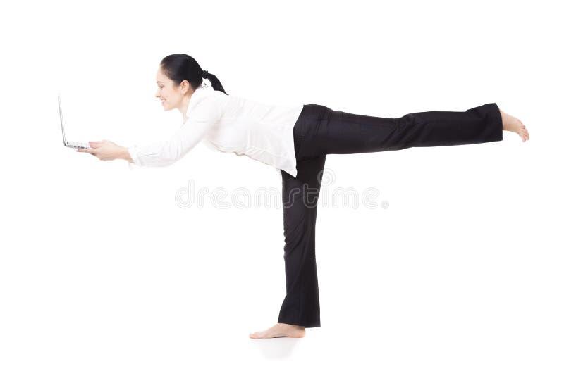 Jeune travailleur d'entreprise dans la pose de yoga tenant l'ordinateur portable sur le dos de blanc photos libres de droits