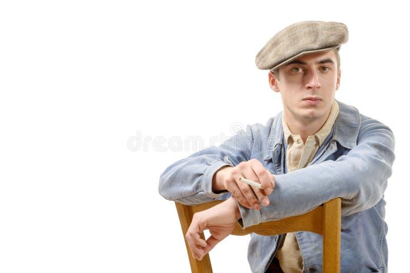 Jeune travailleur dans l'habillement de vintage, se reposant sur une chaise sur un blanc images libres de droits