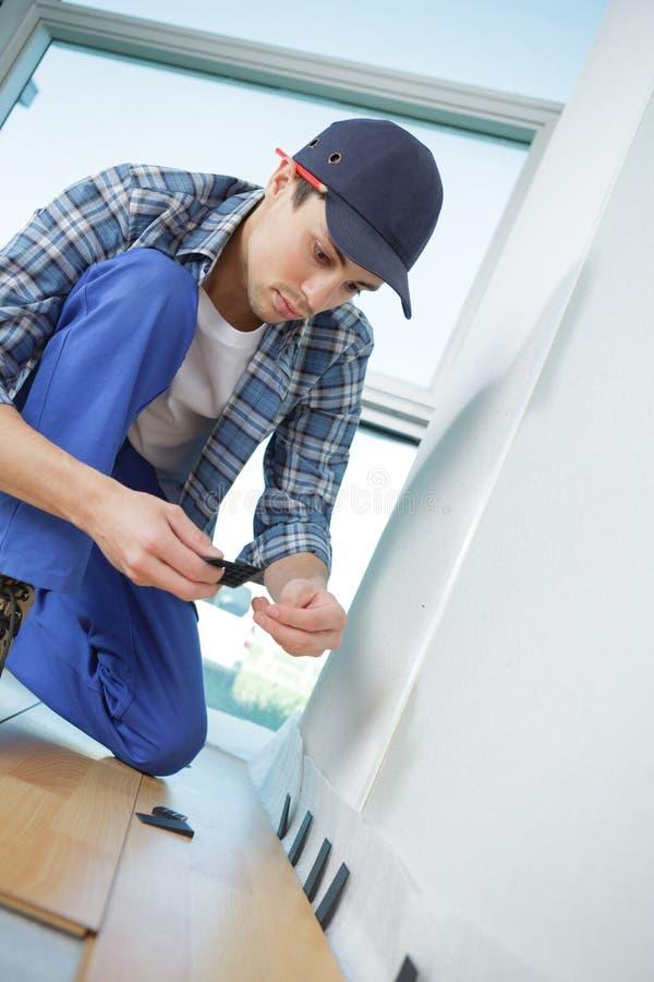 Jeune travailleur dans l'uniforme installant la nouvelle plinthe à la maison photos libres de droits