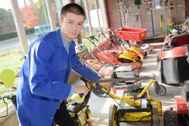 Jeune travailleur dans le magasin de tondeuse à gazon photographie stock