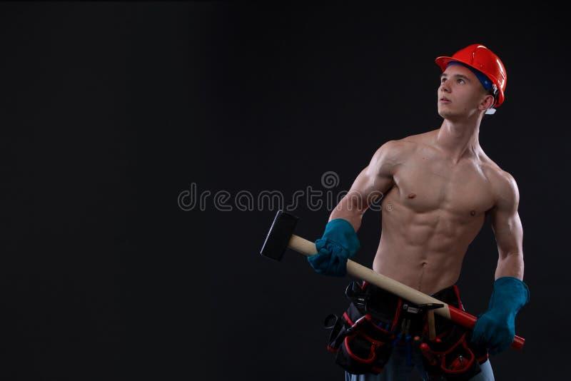 Jeune travailleur de la construction beau de torse nu avec la masse, tir de studio, fond noir Constructeur images libres de droits