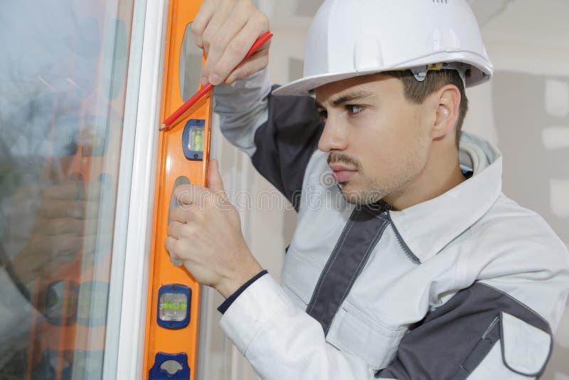 Jeune travailleur de la construction installant la fenêtre dans la maison image libre de droits