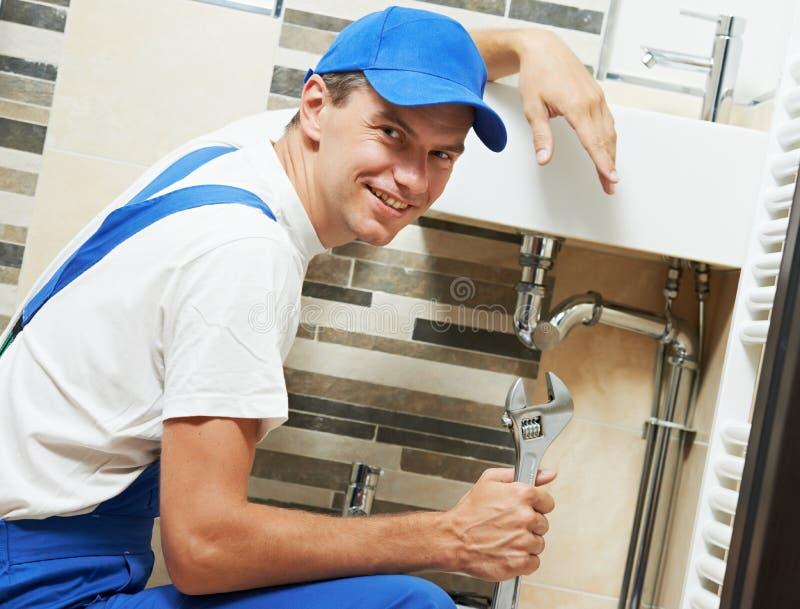 Jeune travailleur de sourire d'homme de plombier photographie stock