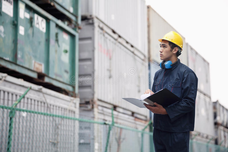 Jeune travailleur en cargaison de examen d'usage protecteur de travail dans une cour de expédition images libres de droits