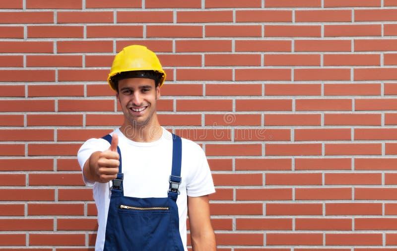 Jeune travailleur montrant le tumb devant un mur de briques photographie stock libre de droits