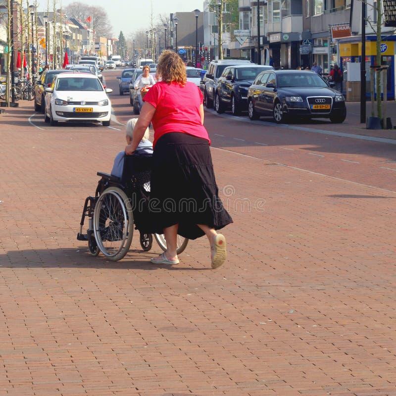 Jeune travailleur social et dame âgée dans un fauteuil roulant, Pays-Bas photographie stock