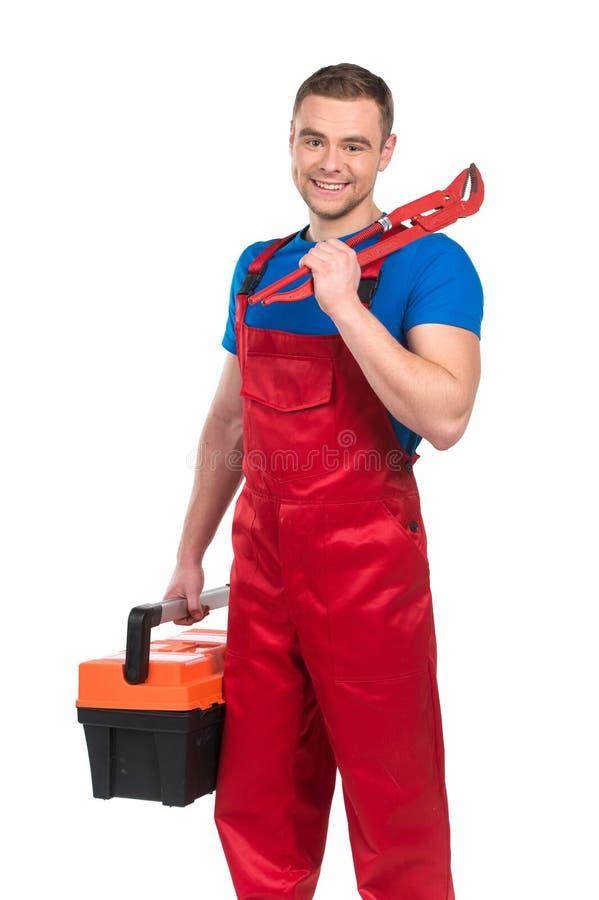 Jeune travailleur tenant la boîte à outils contre le blanc images stock