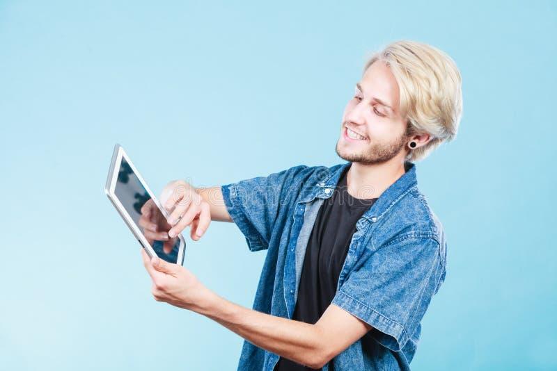 Jeune type à la mode à l'aide de la tablette photographie stock
