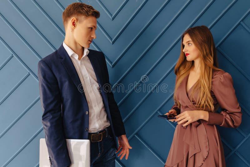 Jeune type élégant avec l'ordinateur portable et la fille avec des émotions de téléphone, fond d'aqua photo stock