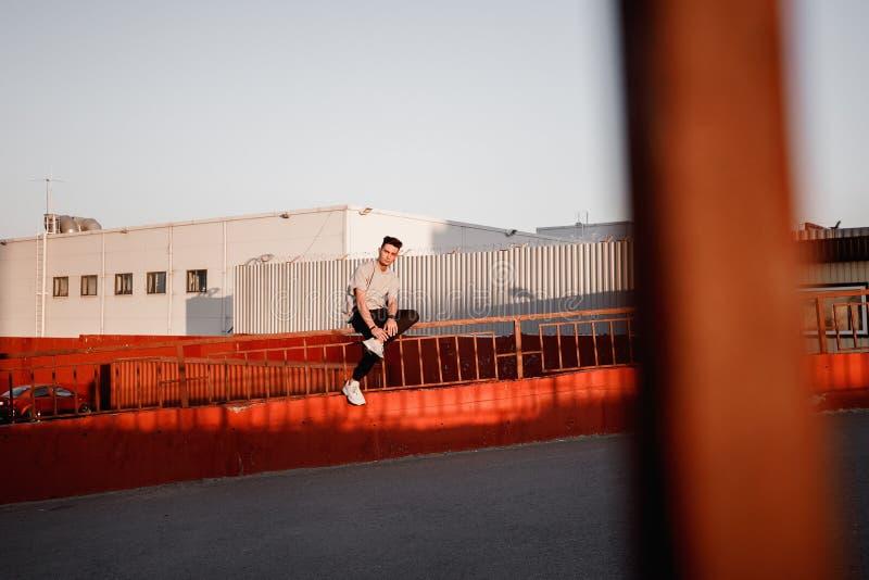Jeune type élégant habillé en jeans et poses blanches de T-shirt à côté du bâtiment urbain avec le stationnement images libres de droits