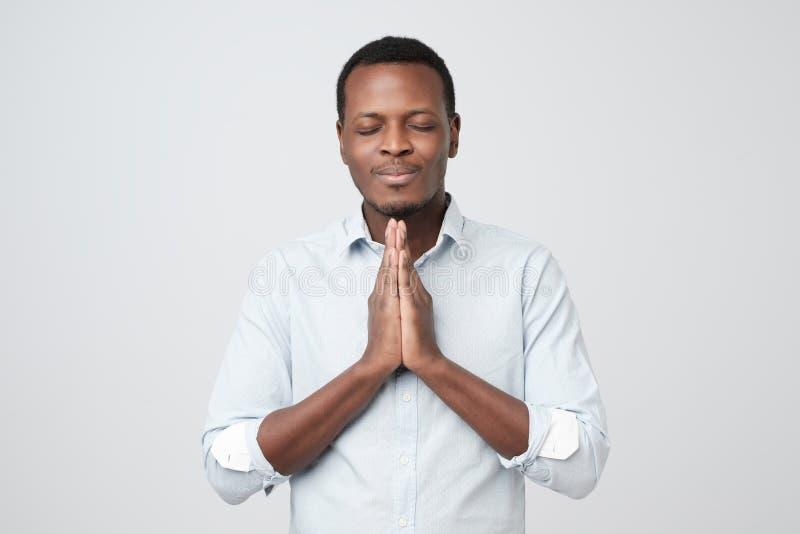 Jeune type africain demandant une faveur Veuillez me couvrir au travail photos stock
