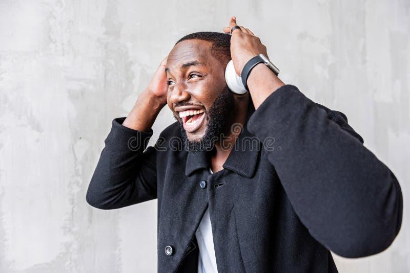 Jeune type africain heureux écoutant la musique par l'intermédiaire du téléphone intelligent image stock