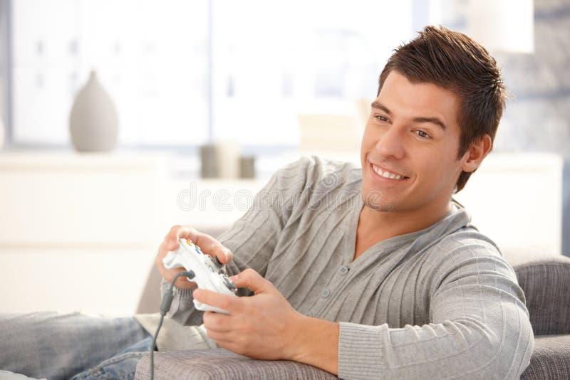 Jeune type appréciant le jeu d'ordinateur images libres de droits