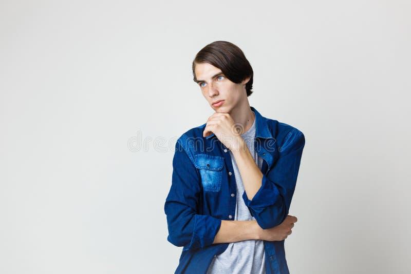 Jeune type aux cheveux foncés mince beau réfléchi avec des yeux bleus utilisant la chemise bleue de denim, tenant la main sur le  image libre de droits