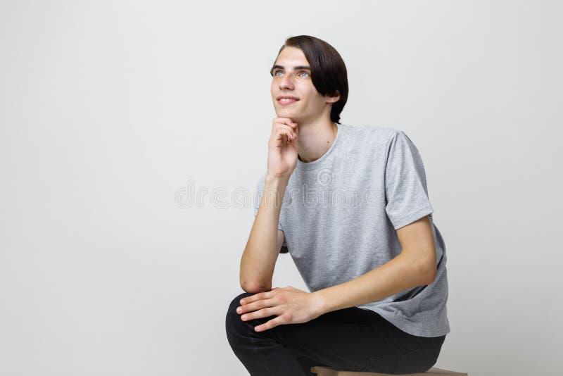 Jeune type aux cheveux foncés mince beau rêveur avec des yeux bleus utilisant le T-shirt gris, regardant à gauche et, se reposant images stock