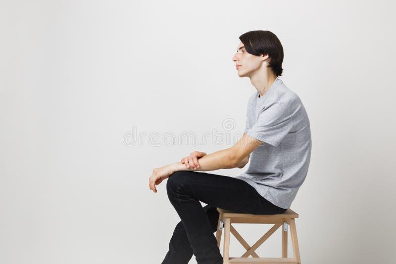 Jeune type aux cheveux foncés mince calme et décontracté avec des yeux bleus utilisant le T-shirt gris, se reposant sur la chaise photo stock