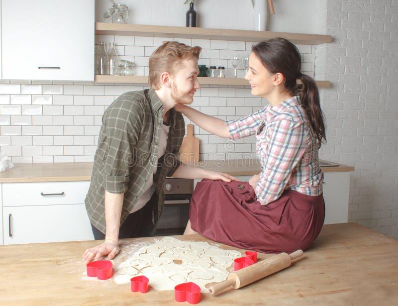 Jeune type avec l'amie étant amoureuse à la cuisine image stock