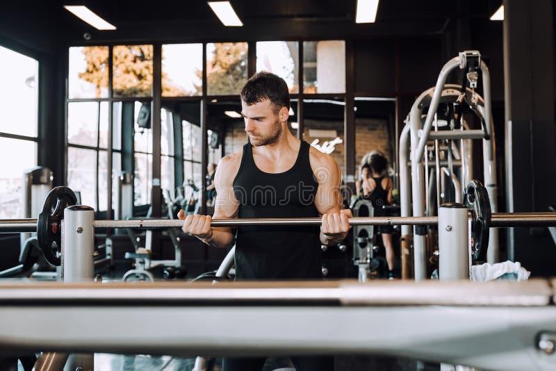 Jeune type avec le corps musculaire avec le barbell dans un gymnase images stock