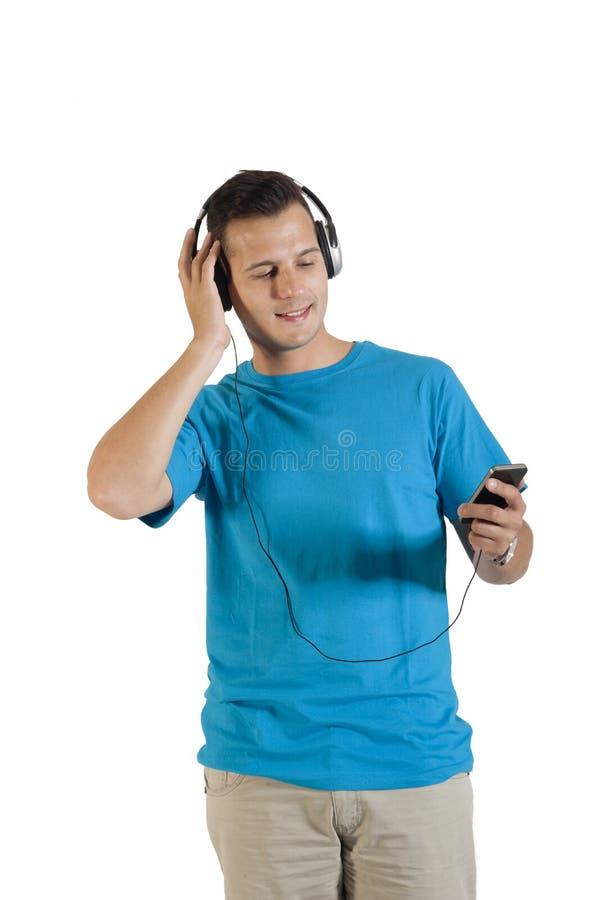 Jeune type beau écoutant la musique outre de son téléphone portable photo libre de droits