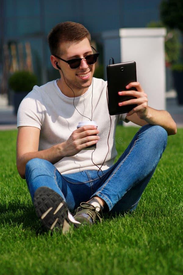 Jeune type beau avec des lunettes de soleil utilisant le comprimé et les écouteurs, café potable à aller, se reposant sur l'herbe photo stock