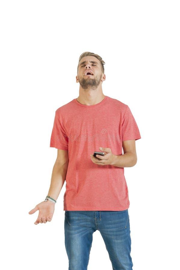 Jeune type beau exaspéré par son téléphone portable image stock