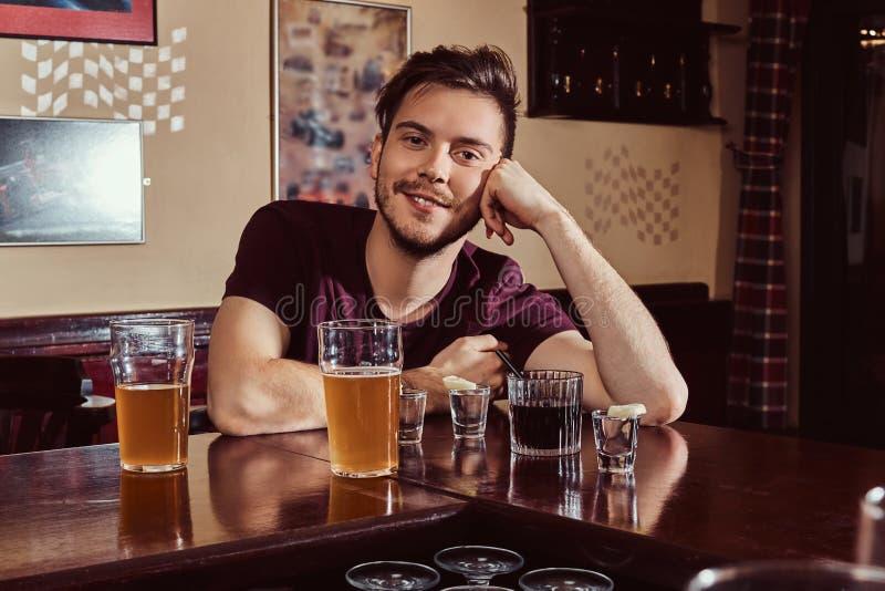 Jeune type beau heureux se reposant dans la barre ou le bar, se reposant avec le verre de bière au compteur en bois photographie stock libre de droits
