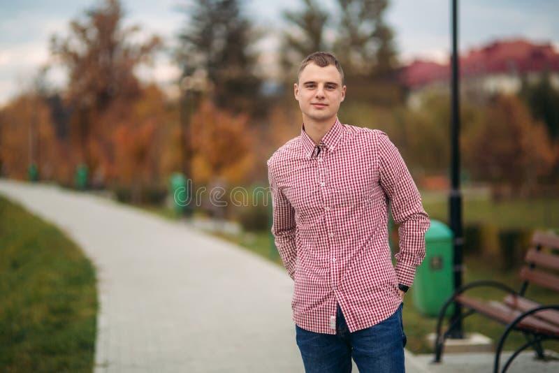 Jeune type dans le séjour rouge de chemise en parc photo stock