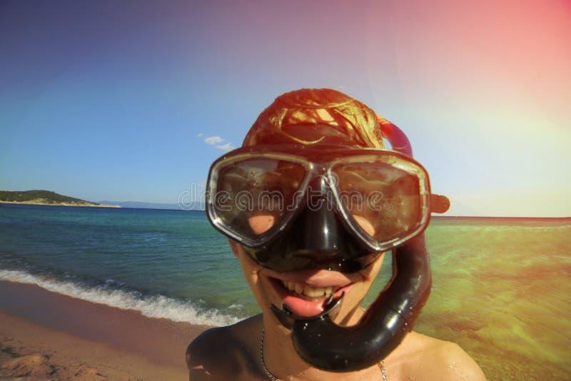 Jeune type dans un masque de plongée contre la mer, objectif grand angle, modifiant la tonalité, Grèce photo libre de droits
