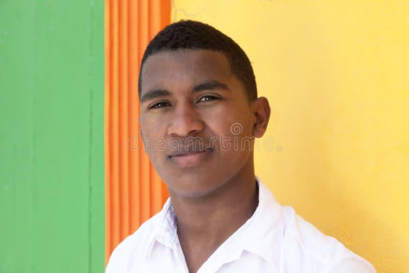 Jeune type des Caraïbes devant un mur coloré images stock