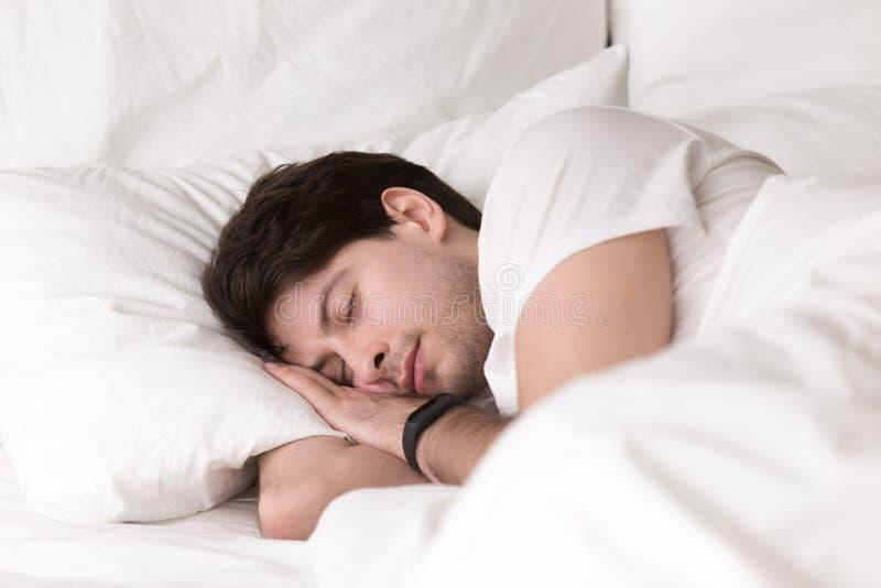 Jeune type dormant dans le smartwatch de lit ou le traqueur de port de sommeil images stock