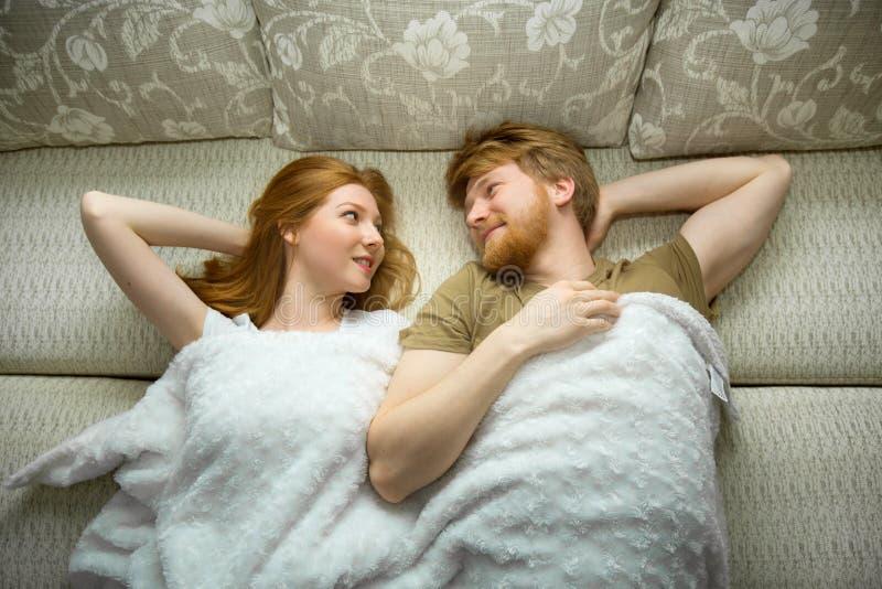 Jeune type heureux de couples avec une fille avec le mensonge rouge de cheveux images stock