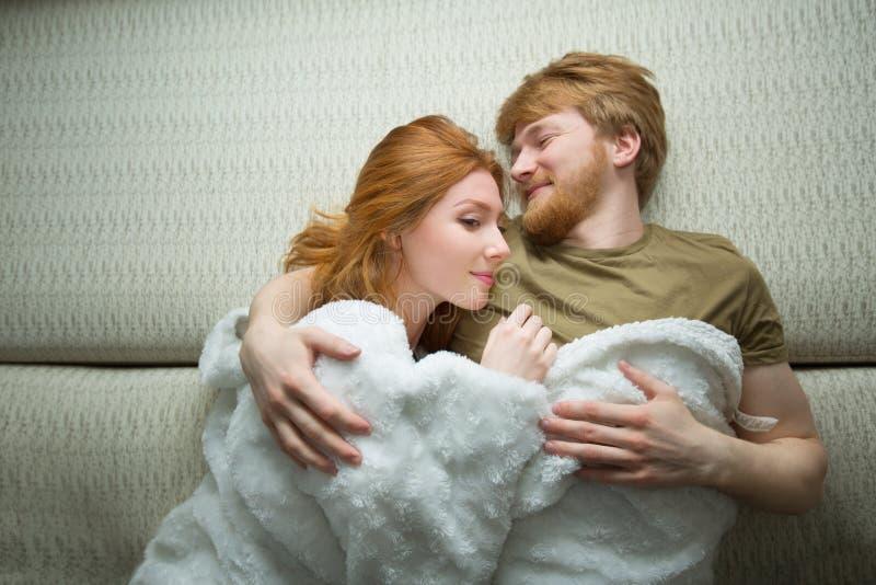 Jeune type heureux de couples avec une fille avec le mensonge rouge de cheveux photographie stock