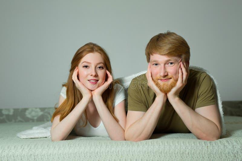 Jeune type heureux de couples avec une fille avec le mensonge rouge de cheveux images libres de droits