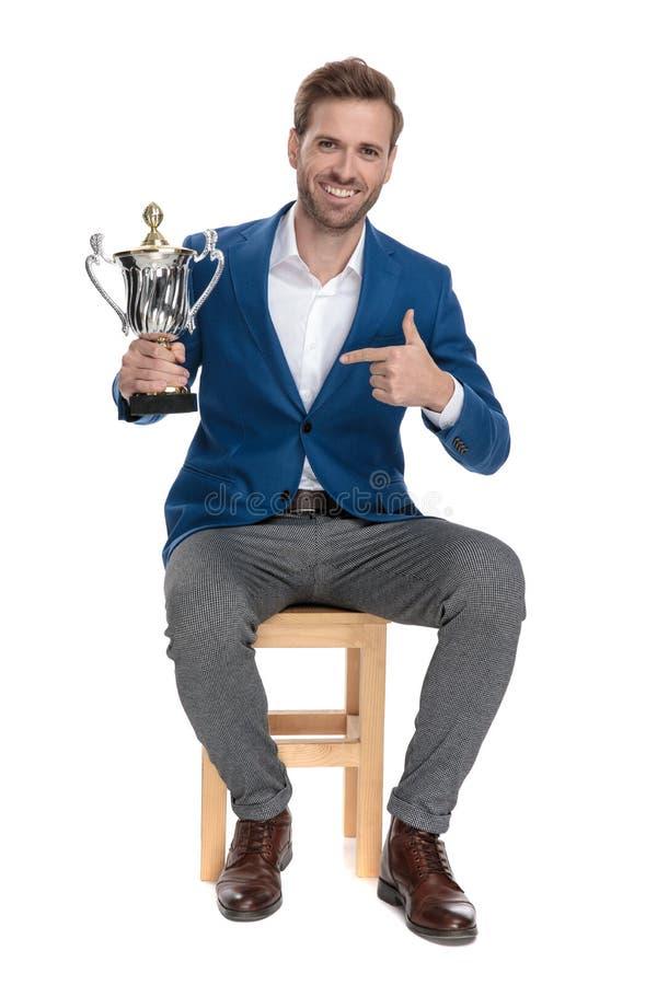 Jeune type occasionnel beau indiquant un trophée image stock