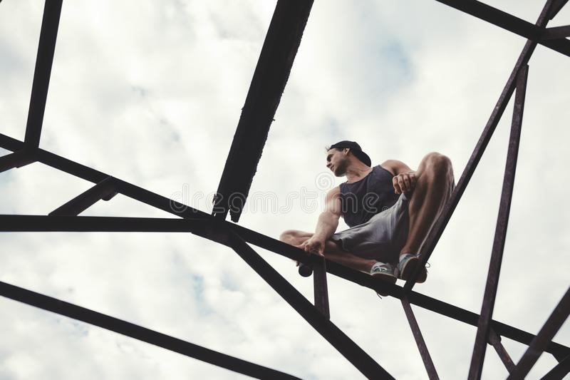 Jeune type risqué équilibrant et s'asseyant sur le dessus de la construction haut en métal photos libres de droits