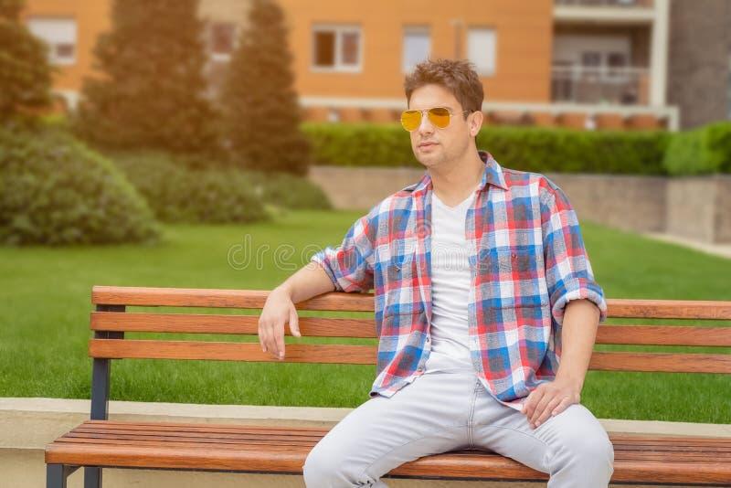 Jeune type s'asseyant sur le banc dehors Mode et personnes urbaines Co photographie stock