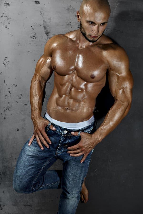 Jeune type sexy musculaire posant dans le studio photos libres de droits