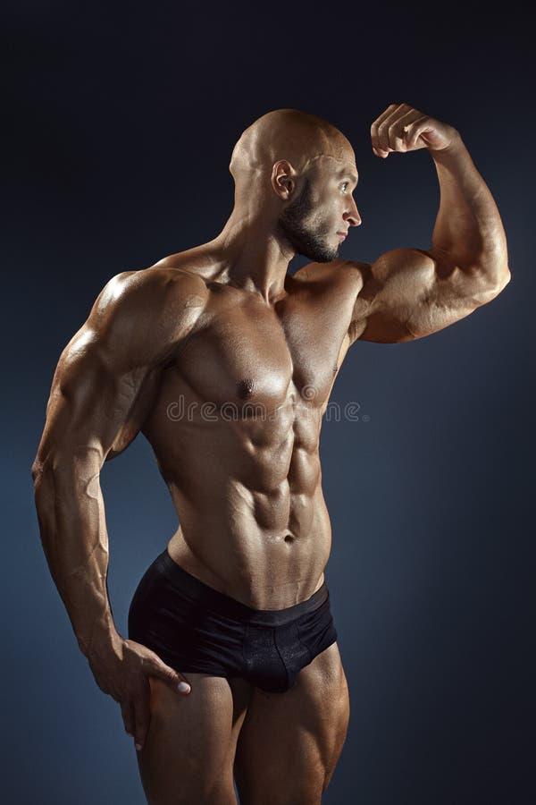 Jeune type sexy musculaire posant dans le studio image stock