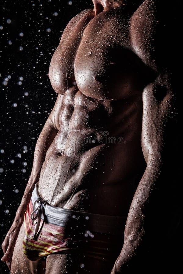 Jeune type sexy sportif musculaire sous la pluie photo libre de droits