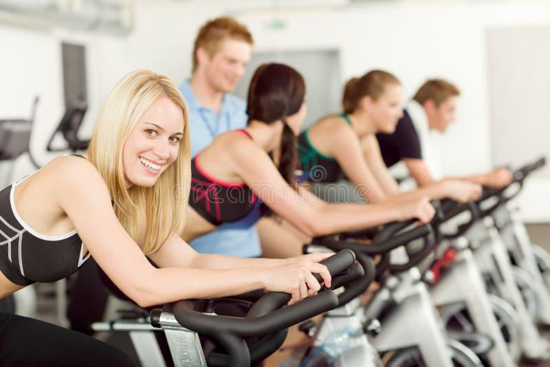 Jeune vélo de gens de forme physique tournant avec l'instructeur photo stock