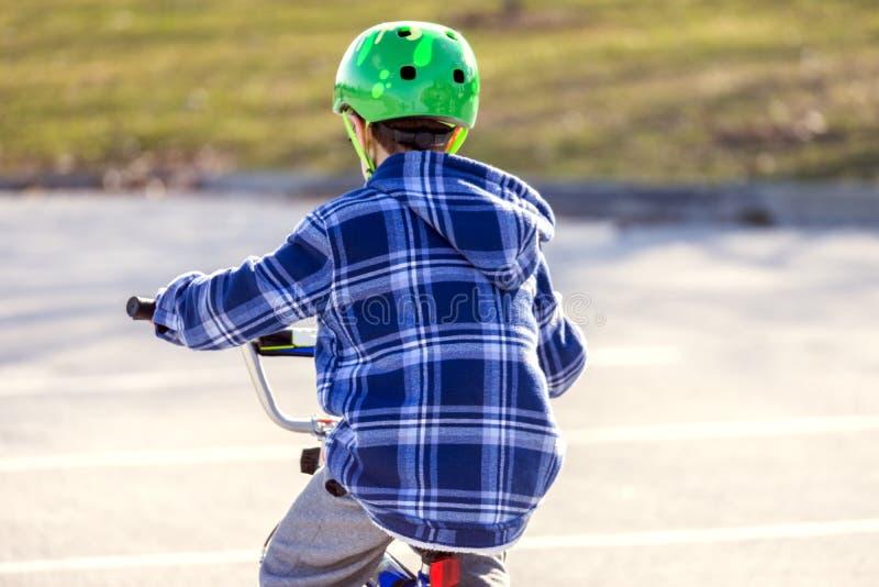 Jeune vélo mignon d'équitation de garçon en soleil de fin de l'après-midi, vue de dos photos stock