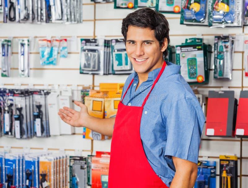 Jeune vendeur souhaitant la bienvenue à la boutique de matériel image stock