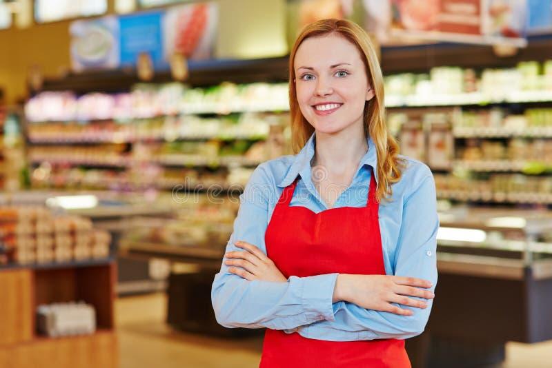 Jeune vendeuse dans le supermarché photographie stock libre de droits