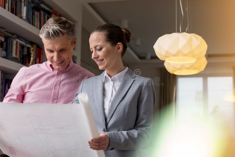 Jeune vendeuse de sourire et client masculin regardant le plan d'étage en appartement photographie stock libre de droits