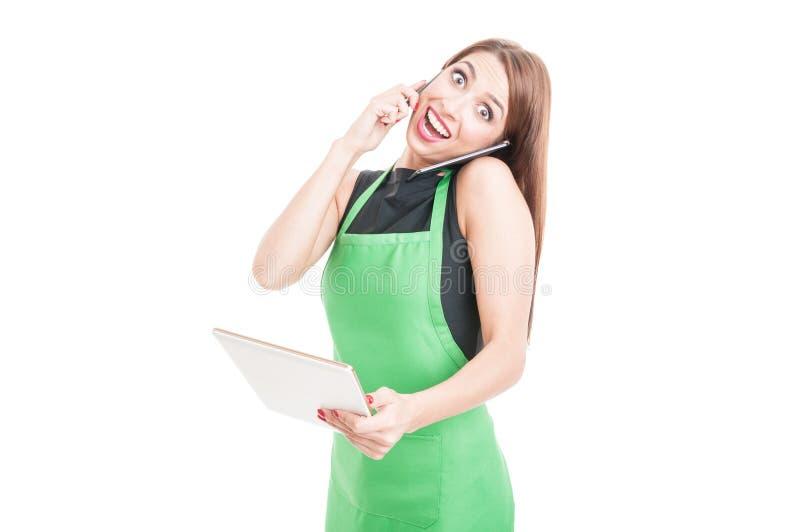 Jeune vendeuse enthousiaste tenant le comprimé photo stock