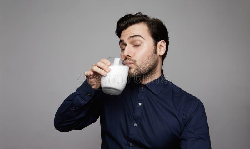 Jeune verre de main sûr de participation d'homme de lait frais sur le fond gris photo stock