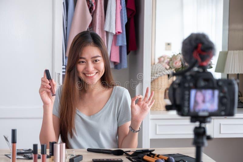 Jeune vidéo femelle asiatique de vlog d'enregistrement de blogger avec le cosm de maquillage image libre de droits