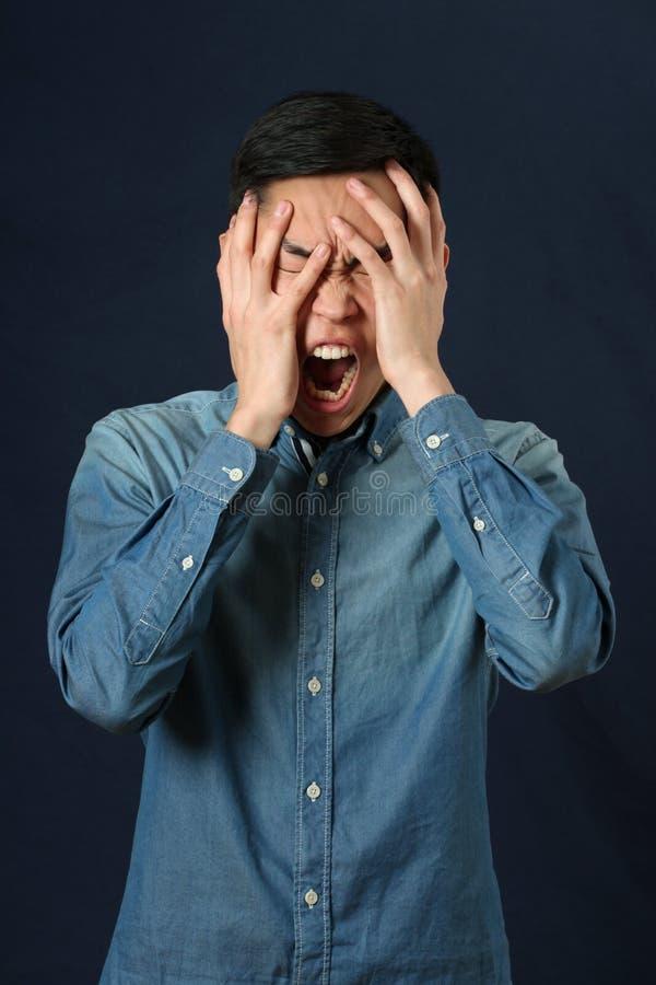 Jeune visage asiatique déçu de bâche d'homme par des paumes photographie stock libre de droits