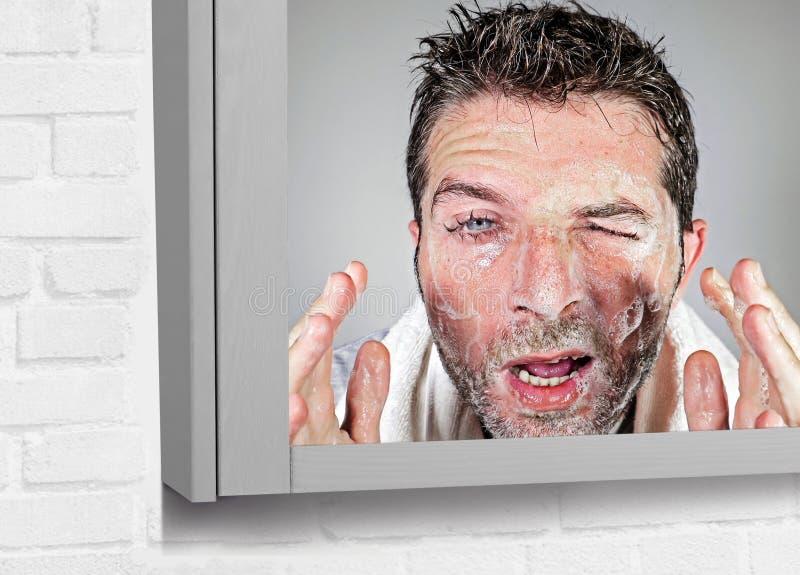 Jeune visage attrayant et drôle de lavage d'homme avec du savon avec les yeux irritants et l'expression malpropre de visage appli image stock