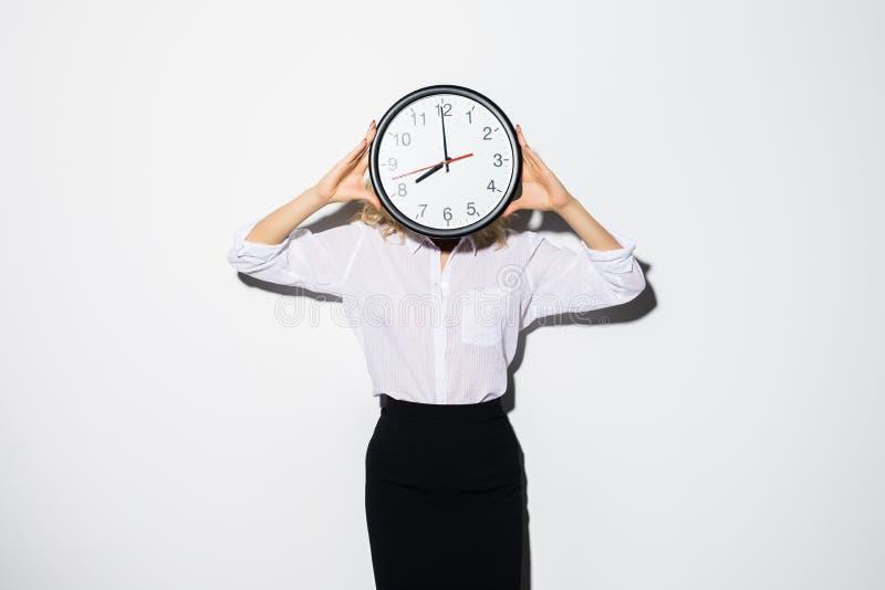 Jeune visage de bâche de femme d'affaires avec la position d'horloge d'isolement au-dessus du fond blanc images stock